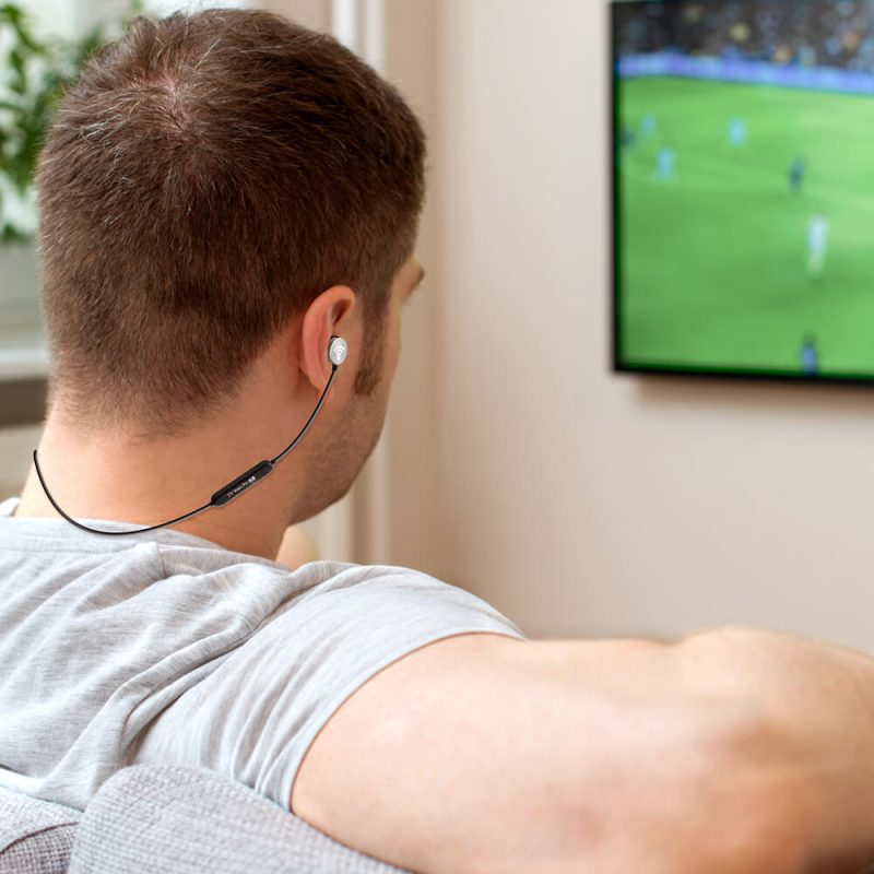 man on couch wearing headphones